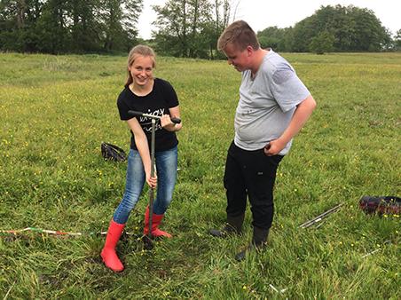 Studenten Hanne en Roy zoeken naar de diepteligging van veen en kleilagen om de metingen van de grondradar mee te vergelijken.